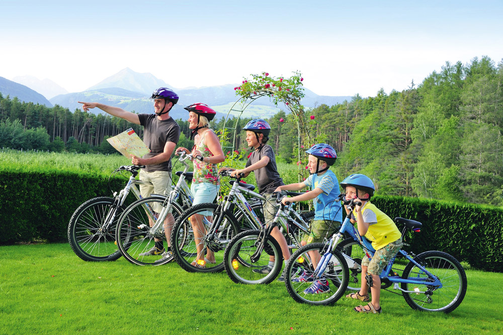 A family stands in front of the hotel with bicycles, which can be rented free of charge at the Hotel Flötscherhof, and plans their route.