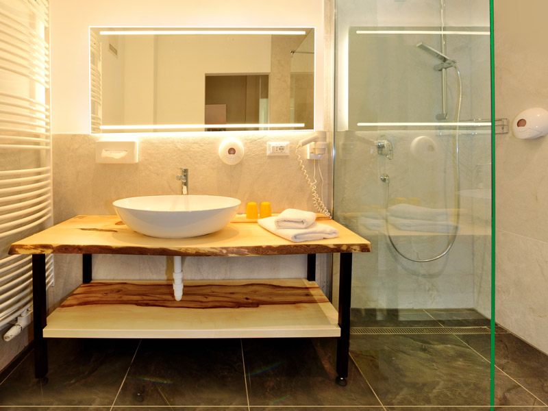 A modern Alpine designed bathroom of a superior room in the Hotel Flötscherhof with a ground-floor shower and a wooden washbasin.