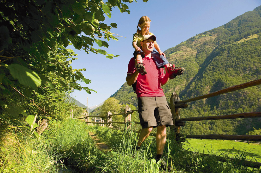 A father carries his daughter on his shoulders on a hiking trail near the Hotel Flötscherhof.