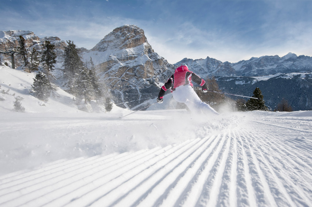 A female skier is skiing through the snow-covered mountain landscape of South Tyrol near the Hotel Flötscherhof.